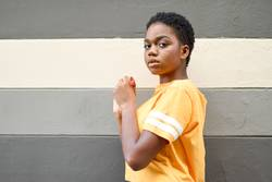 Young black woman with serious expression looking at camera.