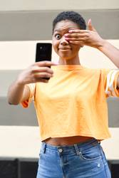 Black woman taking selfie photograph with happy expression