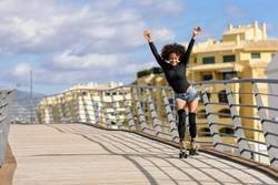 Afro hairstyle woman on roller skates riding outdoors