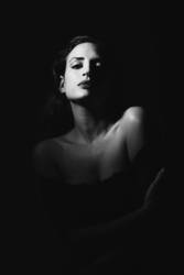 Young woman in black lingerie in chiaroscuro lighting.