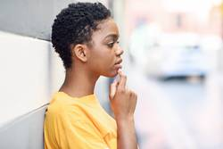 Thoughtful black woman with sad expression outdoors.