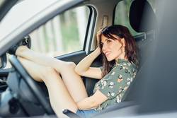 Woman resting in a white car pulling her feet out the window.
