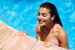 Beautiful Arab woman relaxing in swimming pool.