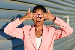 Black woman covering her eyes with her hands.