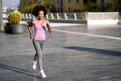 Black woman, afro hairstyle, running outdoors