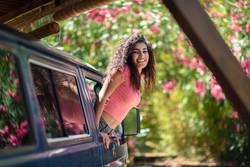 Happy Arab girl peeking out the window of a van