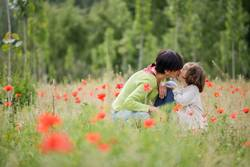 Happy mother kissing her little daughter in poppy field