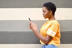 Young black woman using her smart phone outdoors.