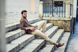 Young smiling man sitting on urban steps