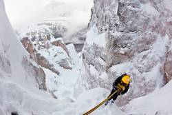 Climber abseiling back down during an extreme winter climbing