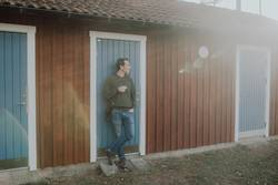 Mann raucht Zigarette im Sonnenlicht vor einem Haus in Schweden