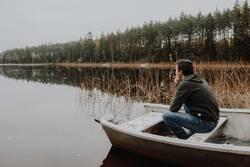 Mann sitzt in Boot am See