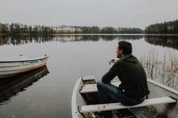 Mann sitzt in Ruderboot auf See und raucht eine Zigarette