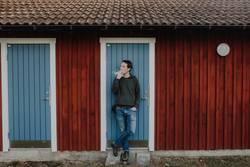 Mann steht vor Schwedenhaus Blockhütte und raucht Zigarette