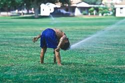 Boy playing in sprinklers.