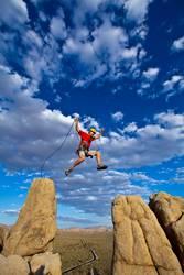 Climber jumping across gap.
