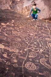 Hiker exploring petroglyph panel.