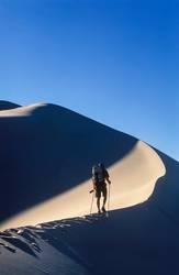 Hiker trekking on sand dunes.