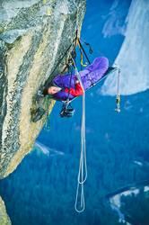 Rock climber sleeping on a clfff.