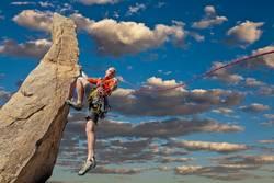 Climber tiptoes on the edge.