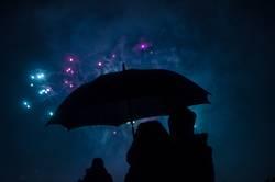 Pärchen unter Regenschirm bei Feuerwerk