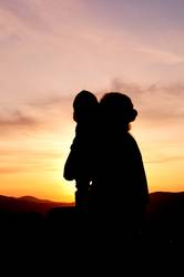 Silhouettes at sunset of a mother and her daughter - Vertical 2