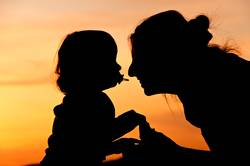 Silhouettes at sunset of a mother and her daughter