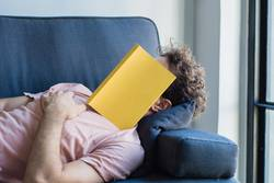 Man sleep on sofa with book cover his face