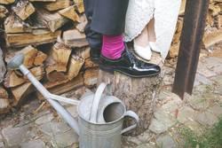 Brautpaarfüße auf Holz an Gießkanne