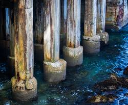 Close Up Aging Pier Pilings in Blue Clear Sea