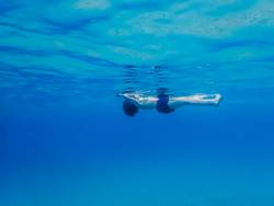 Woman Floats on Surface of Ocean from Underwater
