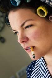 Rauchende Frau mit Lockenwicklern im Haar