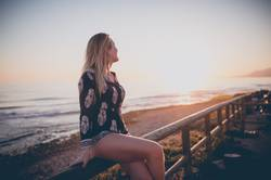 Young woman sitting on railing watching the sunset at the ocean