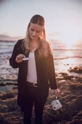 Young woman is looking at polaroid picture at the beach