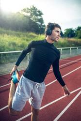 Young man doing stretching at runningtrack with headphones