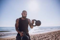 Sports man is doing kettle bells workout at the beach