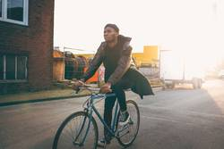 Young modern hipster riding bike trough urban city while sunset