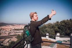Young man is taking selfie at the top of the city