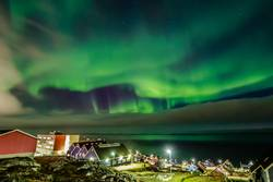 Green bright northern lights hidden by the clouds
