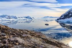 Blick von der felsigen Küste auf die von Gletschern umgebene Bucht von Neco