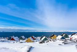Yellow, blue, red and green inuit houses covered in snow
