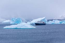 Snowfall and cruise liner among blue icebergs in Port Charcot