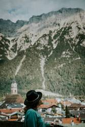 Woman with hat looking out over mountain town