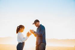 Father and daughter playing hands game on the beach at sunset