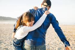 Father and daughter playing piggyback on the beach