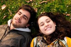 a couple of teenagers lying in the grass
