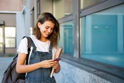 Happy student girl using mobile phone
