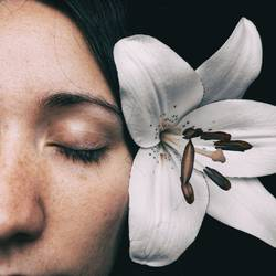 half of a girl's face with a white lily and closed eyes