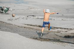 Seven years old boy jumping over the small river
