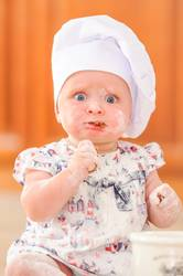 What a look! Cute liitle girl in chef's hat soiled with flour